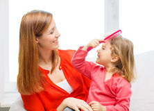 Happy mother and daughter with comb Stock Image