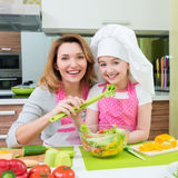 Happy mother and daughter cooking a salad. Stock Photo