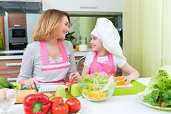Happy mother and daughter cooking a salad. Stock Photos