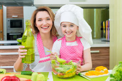 Happy mother and daughter cooking a salad. Portrait of attractive happy mother and daughter cooking a salad at the kitchen royalty free stock photos