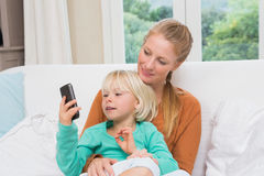 Happy mother and daughter on the couch using smartphone Stock Photos