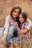 Happy mother and daughter on cozy walk on sunny field Stock Photography