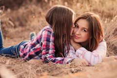 Happy mother and daughter on cozy walk on sunny field Royalty Free Stock Photo