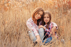 Happy mother and daughter on cozy walk on sunny field Royalty Free Stock Photography