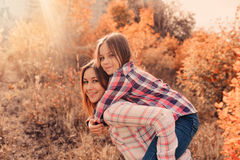 Happy mother and daughter on cozy walk on sunny field Royalty Free Stock Photos