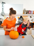 Happy mother with daughter creating Jack-O-Lantern on Halloween Royalty Free Stock Images