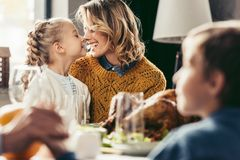 Happy mother and daughter cuddling at thanksgiving. Holiday table royalty free stock photography