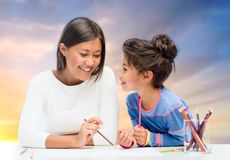 Happy mother and daughter drawing over evening sky Royalty Free Stock Photo