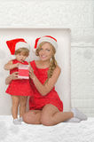 Happy mother and daughter dressed as Santa with gift, snow Stock Photo