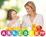 Happy mother and daughter eating breakfast. People, healthy lifestyle, family and food concept - happy mother and daughter eating healthy breakfast over green Royalty Free Stock Image
