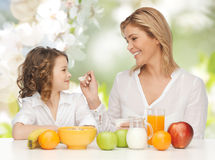 Happy mother and daughter eating breakfast Stock Photography