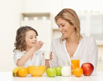 Happy mother and daughter eating breakfast Royalty Free Stock Images