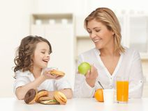 Happy mother and daughter eating breakfast Stock Photo