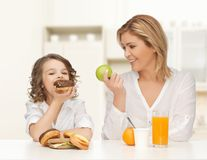 Happy mother and daughter eating breakfast Royalty Free Stock Photos