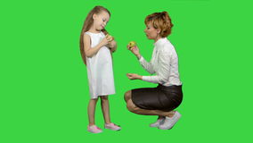 Happy mother with daughter eating healthy food on a green screen, chroma key stock video