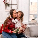 Happy mother and daughter embrace holding gifts. stock image