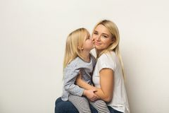 Happy mother and daughter embracing at studio. Happy casual mother and little daughter embracing and kissing at white studio background. Portrait of cute smiling Royalty Free Stock Photos