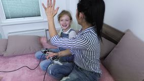 Happy mother and daughter enjoy game. In room stock footage