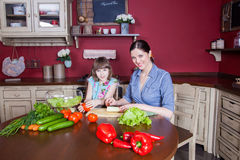Happy mother and daughter enjoy making and having healthy meal together at their kitchen. Royalty Free Stock Image