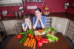 Happy mother and daughter enjoy making and having healthy meal together at their kitchen. Stock Photography
