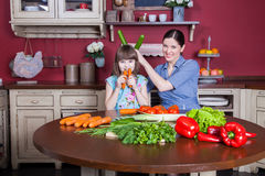 Happy mother and daughter enjoy making and having healthy meal together at their kitchen. Stock Image