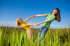 Happy mother and daughter on field. Against the backdrop of blue sky Stock Image