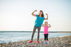 Happy mother and daughter in fitness gear on beach flexing arms Royalty Free Stock Images