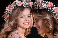 Happy mother and daughter in floral wreaths on black. Beautiful happy mother and daughter in floral wreaths on black Royalty Free Stock Photography