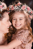 Happy mother and daughter in floral wreaths hugging Stock Image