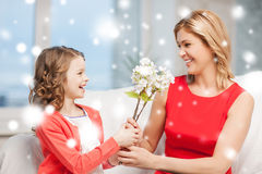 Happy mother and daughter with flowers Stock Images
