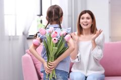 Happy mother and daughter with flowers at home. International Women`s Day stock photography