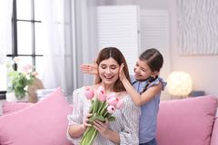Happy mother and daughter with flowers at home. International Women`s Day stock photos