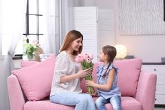 Happy mother and daughter with flowers at home. International Women`s Day stock photo