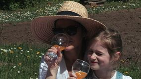 Happy mother and daughter with glasses of juice or lemonade stock footage