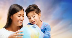 Happy mother and daughter with globe over sky Royalty Free Stock Image