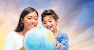 Happy mother and daughter with globe over sky. Family, education, travel and people concept - mother and daughter with globe over evening sky background stock images
