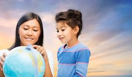 Happy mother and daughter with globe over sky. Family, education, travel and people concept - happy mother and daughter with globe over evening sky background stock images