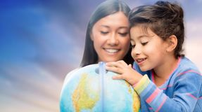 Happy mother and daughter with globe over sky. Family, education, travel and people concept - mother and daughter with globe over evening sky background royalty free stock photos
