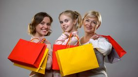 Happy mother, daughter and granny holding shopping bags, female leisure, sale. Stock photo royalty free stock photo