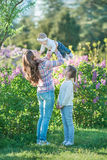 Happy mother and daughter with green apples in the garden of blooming lilacs royalty free stock photos