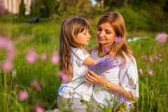 Beautiful young mother and her daughter in white having fun at the flower field in the summer. royalty free stock photography