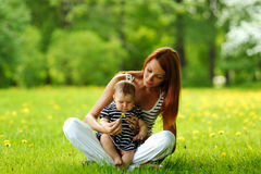 Mother and daughter on the green grass Stock Image