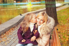 Happy mother with daughter have a rest sitting in autumn park on a bench. Stock Photo