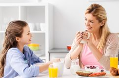 Happy mother and daughter having breakfast at home royalty free stock photos
