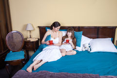 Happy mother and daughter having fun and holding cup and resting in bed. Royalty Free Stock Images