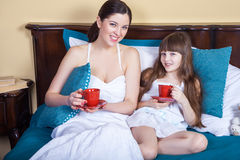 Happy mother and daughter having fun and holding cup and resting in bed. Royalty Free Stock Photography