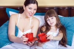 Happy mother and daughter having fun and holding cup and resting in bed. Stock Photography