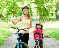 Happy mother and daughter having fun, riding a bicycle and showing thumbs up Stock Photo