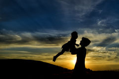Happy mother and daughter having fun at sunset Stock Photo