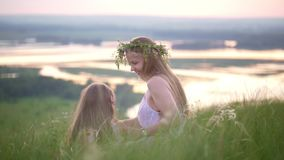 Happy mother and daughter having a rest in nature on the hill at summer sunset stock footage